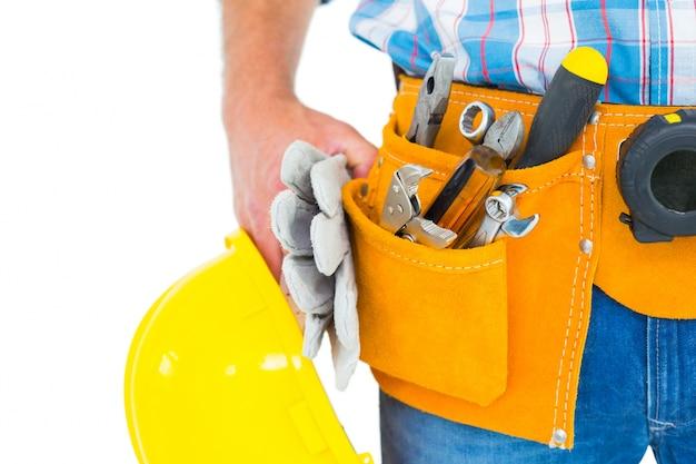 Ręczny pracownik jest ubranym narzędzie pasek podczas gdy trzymający rękawiczki i hełm