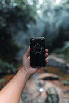 Ręczny smartfon w lesie i kompas, kompas w telefonie