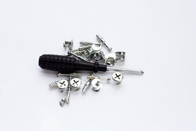 Ręczny śrubokręt i śruby na białym tle.