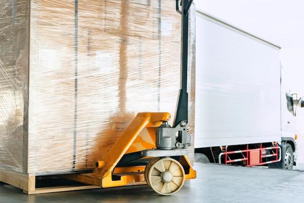 Ręczny wózek paletowy lub podnośnik paletowy z przesyłką kurierską na palecie.