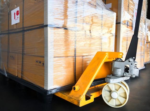 Ręczny wózek paletowy z paletą ładunkową. przesyłka do transportu.