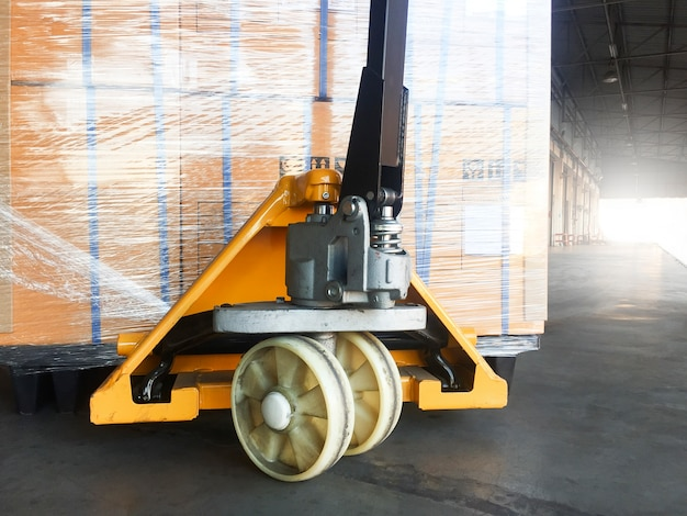 Ręczny wózek paletowy z paletą wysyłkową do wywozu.