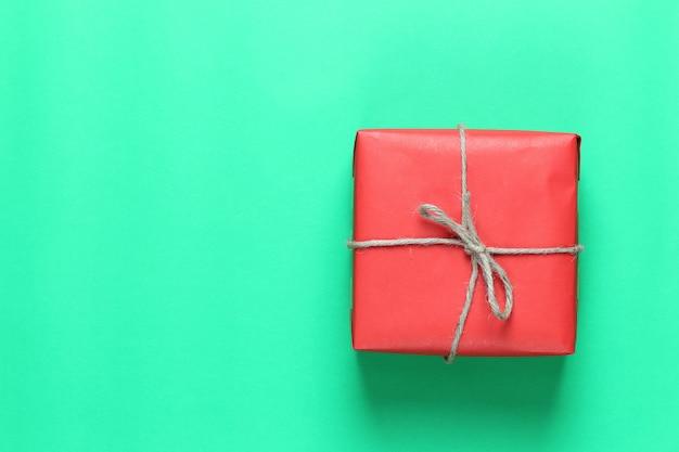 Red christmas gift box umieszczone na zielonej podłodze papieru sztuki i kopia przestrzeń.