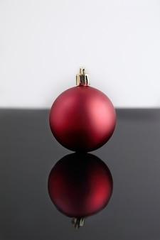 Red golden christmas ball odzwierciedlenie na czarnym stole i białym tle. skopiuj miejsce.