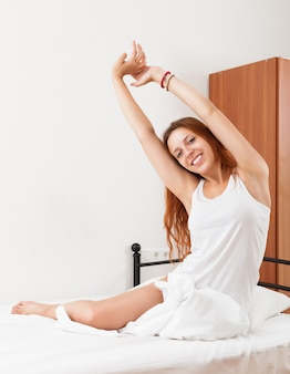 Red-haired zmysłowa dziewczyna w koszuli awaking na białym arkuszu w łóżku w domu