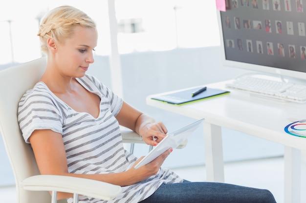 Redaktor zdjęć blond pracuje na komputerze typu tablet