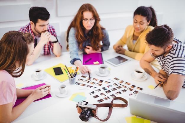 Redaktorzy omawiają zdjęcia podczas spotkania w biurze kreatywnym
