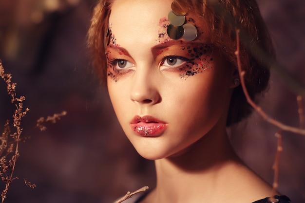 Redhair kobieta z jaskrawym kreatywnie makijażem