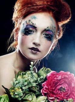 Redhair piękna kobieta trzyma kwiaty