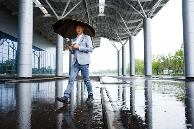 Redhaired biznesmen z parasolem picia kawy