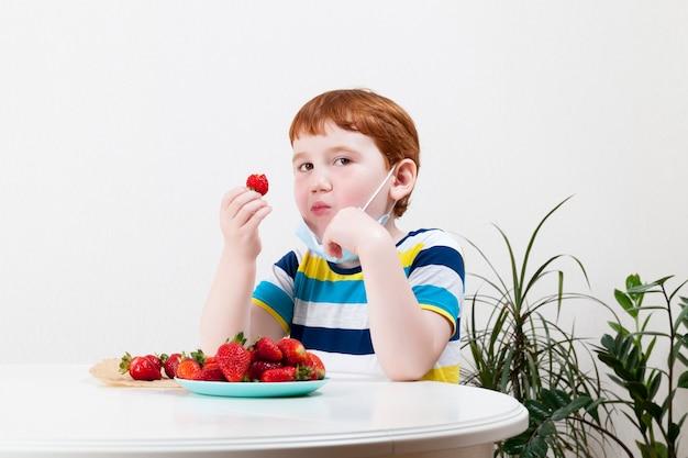 Redhaired chłopiec jedzenie dojrzałe czerwone truskawki