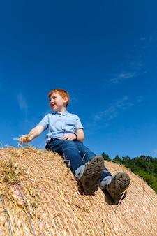 Redhaired chłopiec siedzi na złotym stosie słomy