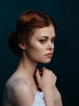 Redhaired kobieta w białej sukni pozuje atrakcyjny wygląd studyjny