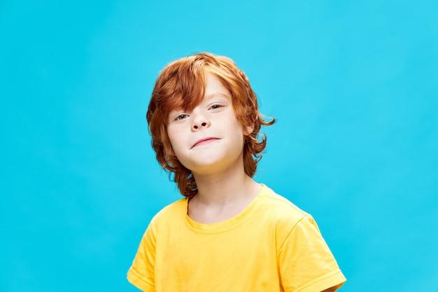Redhead boy grymas żółta koszulka emocje niebieskie tło