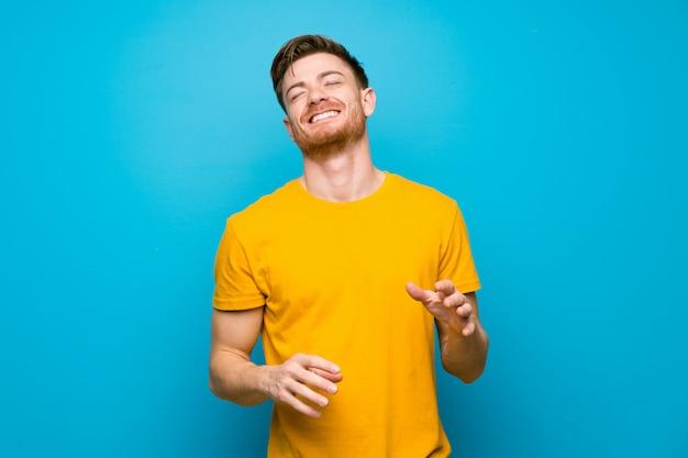 Redhead człowiek na niebieską ścianą uśmiechnięty