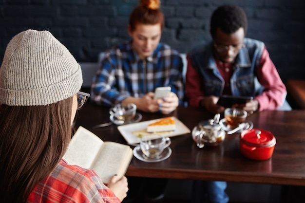 Redhead kobieta dokonywania zamówienia online podczas zakupów przez internet w telefonie komórkowym podczas lunchu w nowoczesnym wnętrzu kawiarni z przyjaciółmi. selektywne skupienie się na nierozpoznawalnej kobiecie, która czyta książkę