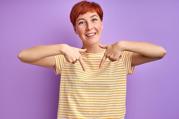 Redhead kobieta wskazując palcem w dół i uśmiechnięta, kopia przestrzeń. odizolowane na fioletowej ścianie