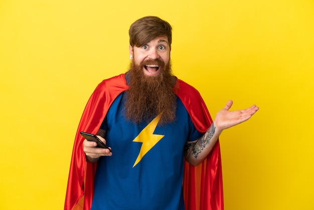 Redhead super hero mężczyzna na białym tle na żółtym tle prowadzenie rozmowy z telefonem komórkowym z kimś