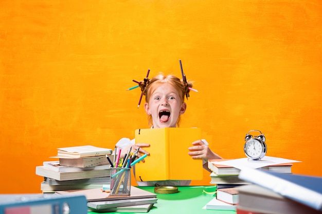 Redhead teen girl z dużą ilością książek w domu. strzał studio