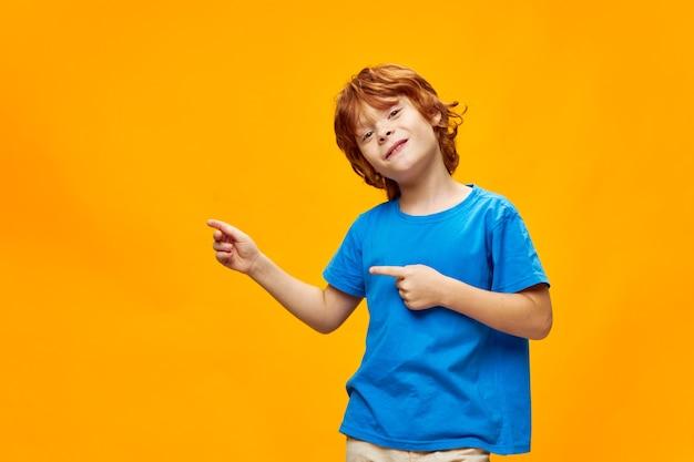 Redheaded boy niebieski t-shirt żółte tło piegi i wolna przestrzeń, wskaż palcem w bok