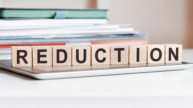 Redukcja wyrazów zapisana jest na drewnianych kostkach stojących na notatniku, na powierzchni stosu dokumentów