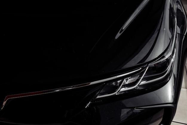 Reflektor nowoczesnego prestiżowego czarnego samochodu z bliska. zamyka w górę fotografii nowożytny samochód, szczegół reflektor. projektor led reflektorów samochodowych w nowoczesnej luksusowej technologii i detalach samochodowych. selektywna ostrość