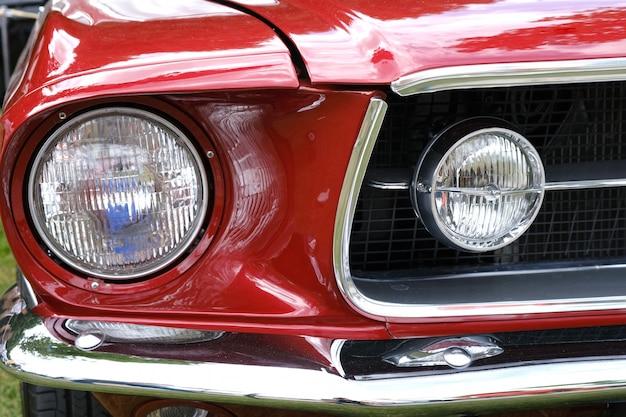 Reflektory, chłodnica i maska retro czerwonego samochodu z bliska.