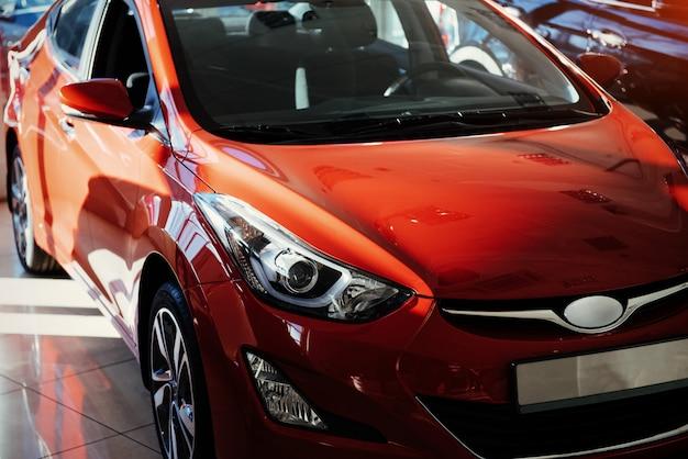 Reflektory i maska sportowego czerwonego samochodu.