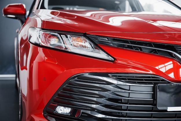 Reflektory nowego czerwonego samochodu w salonie samochodowym.