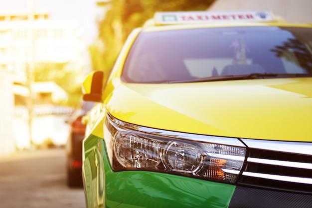 Reflektory taksówek na rogu ulicy z promieni słonecznych. w tle, taxi i samochód.