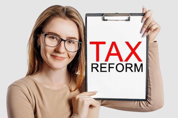 Reforma podatkowa. piękna młoda biznesowa kobieta w okularach trzyma schowek z makietą miejsca na szarym tle