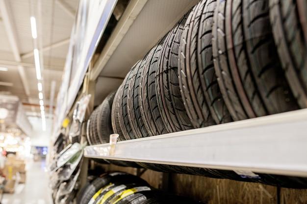Regał z różnymi oponami samochodowymi w sklepie samochodowym