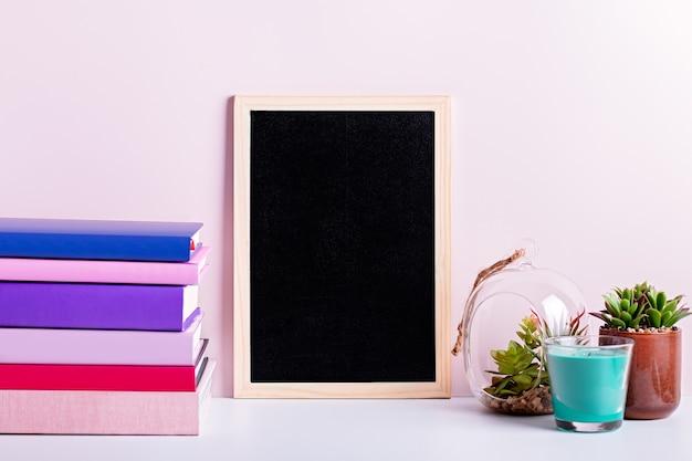 Regał z wielokolorowymi książkami, sukulentami roślin doniczkowych i ramą czarnej tablicy na tekst. tło na dzień nauczyciela, światowy dzień książki. martwa natura ze stosem kolorowych książek, tablica