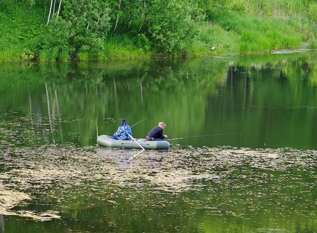 Region nowosybirsk syberia rosja06132021 rybacy na powierzchni leśnego jeziora