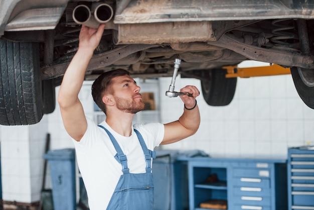 Regulacja kół. pracownik w niebieskim mundurze pracuje w salonie samochodowym.