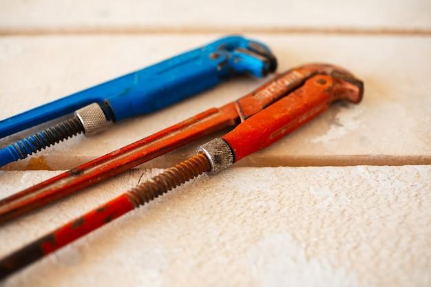 Regulowane klucze gazowe w kolorze niebieskim i czerwonym na drewnianym stole.