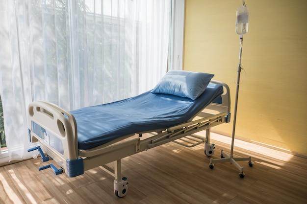 Regulowane łóżko pacjenta w sali szpitalnej z ciepłym światłem.