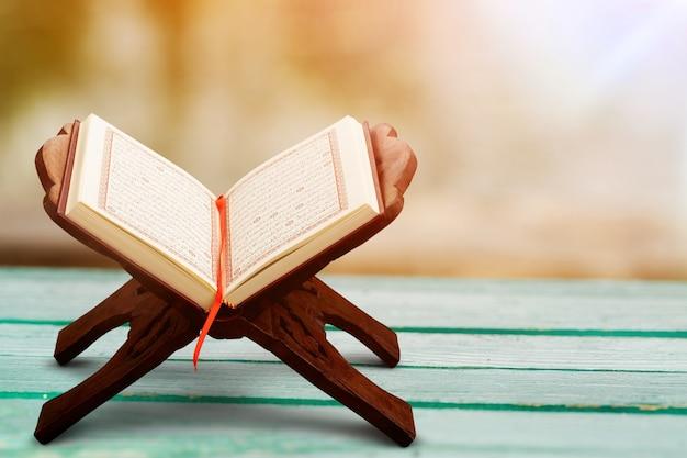 Rehal z otwartym koranem na muzułmańskiej macie modlitewnej w pomieszczeniu. miejsce na tekst - obraz