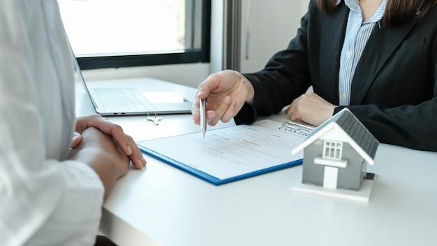 Ręka agenta nieruchomości trzyma długopis i wyjaśnia kobiecie klienta umowę biznesową