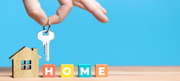 Ręka agenta nieruchomości z kluczem i modelem domu na niebieskim tle. wielokolorowe drewniane klocki ze słowem home.