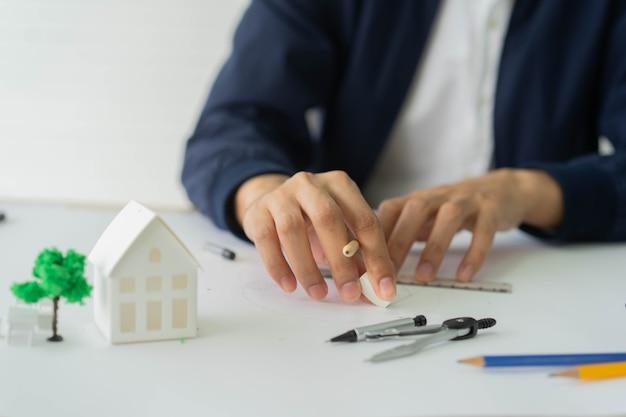 Ręka architekta używająca gumki do usuwania szkiców na papierze projektowym z projektu mieszkaniowego