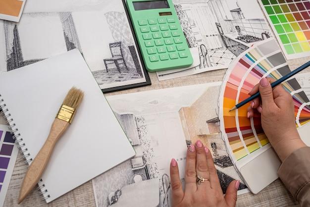Ręka architekta wnętrz wybiera kolor z palety. koncepcja renowacji