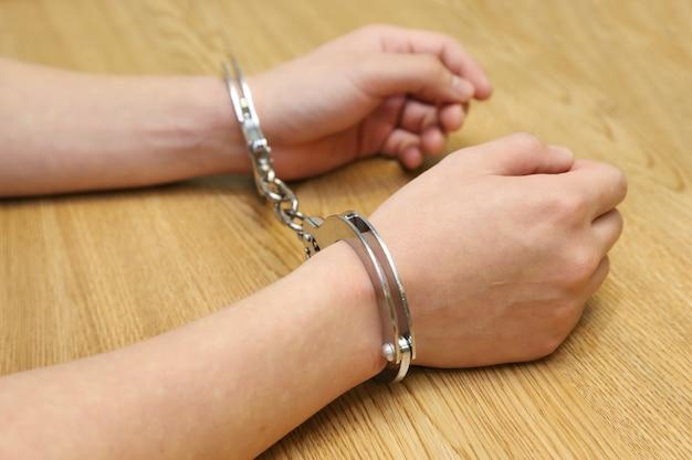 Ręka aresztowana z kajdankami na drewnianym stole