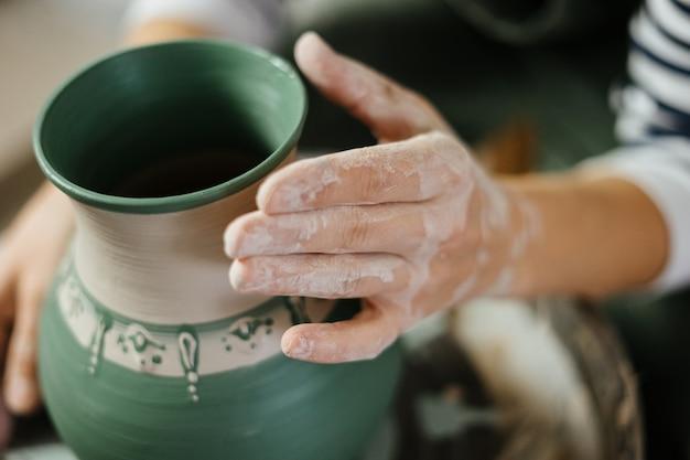 Ręka artysty obok ręcznie malowanego garnka w warsztacie ceramicznym. garncarstwo. umiejętności ceramiczne.
