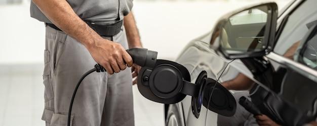 Ręka azjatyckiego technika banner of zbliżenia ładuje samochód elektryczny lub ev w centrum serwisowym w celu konserwacji, ekologicznej koncepcji energii alternatywnej, osłony i banerów
