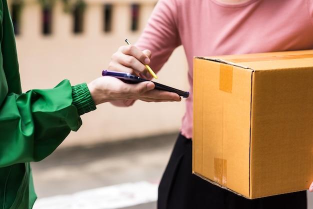 Ręka azjatyckiej kobiety dołączającej podpis podpisu na smartfonie po zaakceptowaniu odbierania pudełek od dostawy mężczyzny w mundurze. nowa normalna działalność dostawcza podczas pandemii covid19. zakupy internetowe.