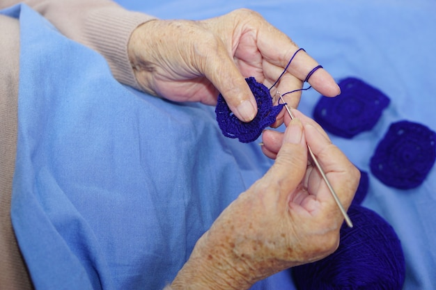 Ręka azjatyckiej starszej kobiety szydełkowej ciemnoniebieskiej przędzy