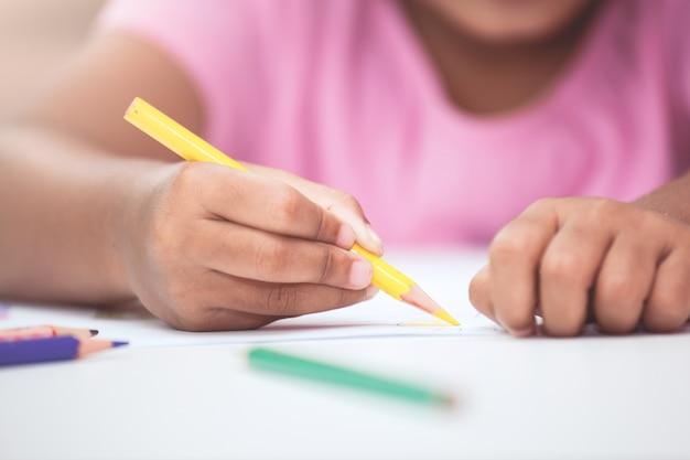 Ręka azjatykcia dziecko dziewczyna rysuje i maluje z kredką w rocznika koloru brzmieniu
