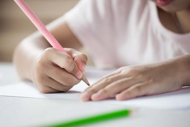 Ręka azjatykcia dziecko dziewczyna rysuje i maluje z kredką