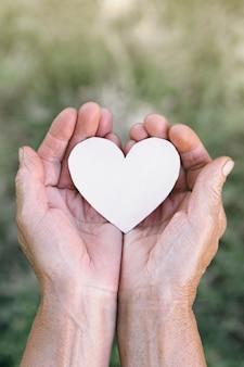 Ręka babci trzyma serce